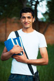 Arab male student with books outdoors. Looking very happy Royalty Free Stock Photography