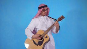 Arab man with an acoustic guitar. On a blue background stock footage
