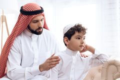 Arab man asks for forgiveness from small offended son. Arab men asks for forgiveness from small offended son. Relationship between father and son royalty free stock images