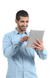 Arab man browsing a tablet reader with finger. Isolated on a white background Royalty Free Stock Images