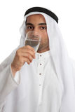 Arab man drinking pure fresh water. An arab middle eastern man wearing traditional clothing, is drinking a tall glass of clean fresh water. Water shortage stress Royalty Free Stock Photos