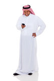 Arab man email phone. Cheerful Arab man  reading email on smart phone isolated on white Royalty Free Stock Images