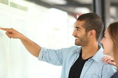 Arab man and friend consulting schedule in a station royalty free stock photos