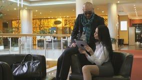 Arab man and girl looking photos on digital tablet stock footage
