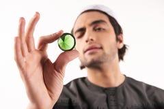 Arab man looks at precious green stone. stock image