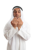 Arab man with open palms praying. An arab middle eastern man dressed in traditional rob and headdress with open hands praying royalty free stock image