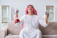 The arab man with prize and money on sofa Stock Photography