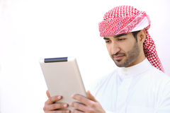Arab man reading a tablet outdoor on white Stock Photos