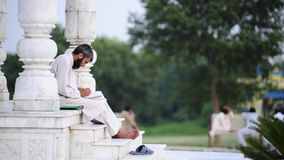 Arab man reading and writing from  book. Islamabad. Pakistan stock footage