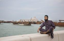 An arab man resting and looking at boats Royalty Free Stock Photo
