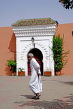 An Arab man runs in front of an arched door of the Marrakesh Mosque Stock Images