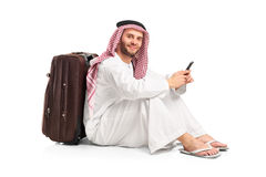 Arab man sitting near a suitcase Stock Images