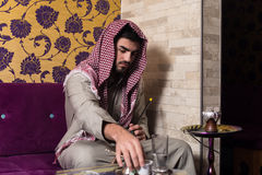 Arab Man Smoking Shisha And Drinking Coffee Royalty Free Stock Images