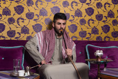 Arab Man Smoking Shisha And Drinking Coffee Royalty Free Stock Photography