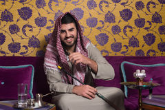 Arab Man Smoking Shisha And Drinking Coffee Stock Photo