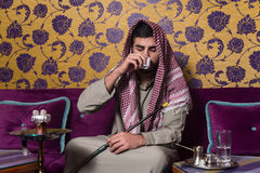 Arab Man Smoking Shisha And Drinking Coffee Stock Image