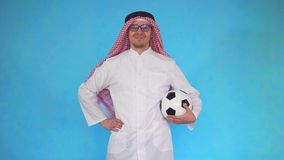 Arab man with soccer ball. Stands on a blue background stock footage