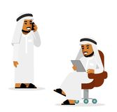 Arab man in tablet pc and smartphone internet working concept. Young saudi arabic man sitting with tablet computer, standing and using mobile phone Stock Photo