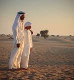 Arab man and a teenager in the desert and watch the sunset. DUBAI, UAE - NOVEMBER 12, 2013: Arab man and a teenager in the desert and watch the sunset Royalty Free Stock Photos