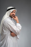Arab man thinking hard with hand on his face Stock Photo