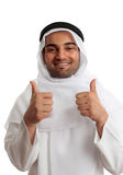 Arab man thumbs up success. Ethnic man giving a thumbs up approval.  He is wearing cultural clothing, white thawb, ghutra and double black rope called an Igal Stock Image