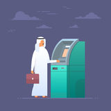 Arab Man Using Atm Machine Taking Money From Credit Card, Islam Businessman Wearing Traditional Clothes Stock Image