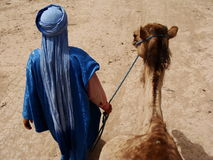 Arab man walking camel Royalty Free Stock Photos