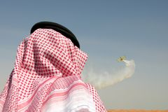 Arab man watching airshow. Over the desert Royalty Free Stock Image