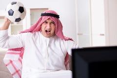 The arab man watching tv at home. Arab man watching tv at home Royalty Free Stock Image