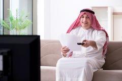 The arab man watching tv at home. Arab man watching tv at home Royalty Free Stock Photography