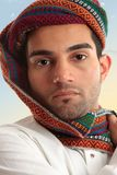 Arab man wearing turban. Arab man wearing a colourful wovan keffiyeh or turban style  head piece.  These headdresses serve a purpose of protecting nose and mouth Royalty Free Stock Images