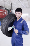 Arab mechanic with tire and spanner. Picture of Arab mechanic holding a tire and spanner while wearing uniform in the workshop Royalty Free Stock Photo