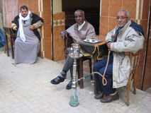Arab men drinking coffee and smoking the narguile Stock Photography
