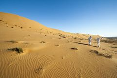Arab men with turban, desert tour guides walking in desert Royalty Free Stock Photo
