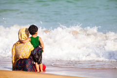 Arab mother and son hugging to the sea