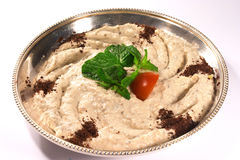 Arab moutabel. A tray of moutabel, a traditional Arabic eggplant dip, commonly served as mezze, topped with mint and a small tomato Royalty Free Stock Photos