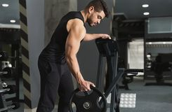 Muscular sportsman taking weights from a rack in gym. Arab muscular sportsman taking weights from a rack in gym, copy space stock photos