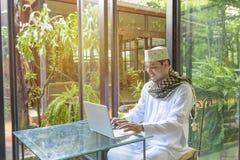 Arab muslim business man dress in white thobe with prayer cap an Stock Photo