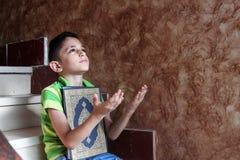 Arab muslim child with koran holy book stock photo