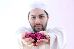 Arab muslim man with dried flower showing peace Stock Photos