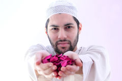 Arab muslim man with dried flower showing peace. Arab egyptian muslim man wearing islamic clothes and holding dried flowers which represent peace stock images