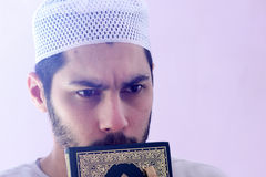 Arab muslim man with koran holy book. Arab egyptian muslim man wearing islamic clothes and holding Koran holy book stock images