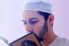 Arab muslim man with koran holy book. Arab egyptian muslim man wearing islamic clothes and holding Koran holy book Royalty Free Stock Photography