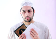Arab muslim man with koran holy book and pc tablet Stock Images