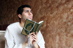 Arab muslim man with koran holy book with rosary Stock Photos