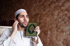 Arab muslim man with Koran islamic holy book and headset Stock Image