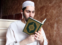 Arab muslim man with Koran islamic holy book and headset Stock Photography