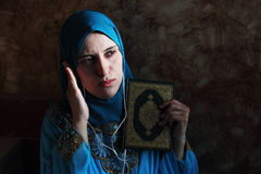 Arab muslim woman with Koran islamic holy book and headset Stock Photos