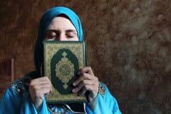 Arab muslim woman with Koran islamic holy book and headset Royalty Free Stock Photography