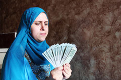 Arab muslim woman with money. Photo of arabian egyptian muslim woman holding dollar bills money royalty free stock photography